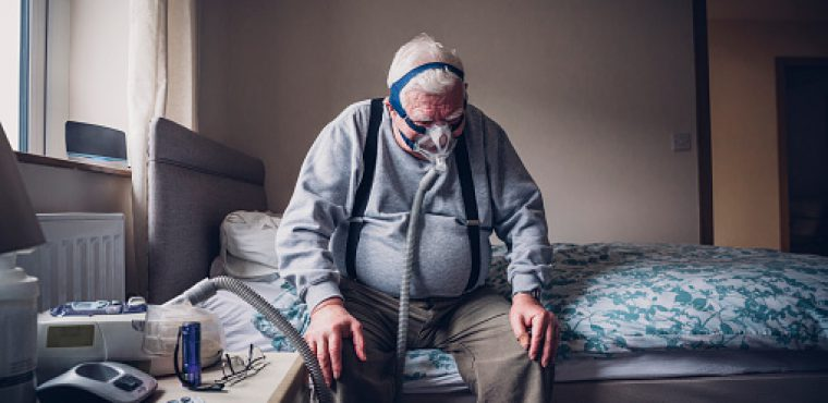 Elderly man sitting at home on his bed. He is wearing a medical breathing apparatus over his face attached to a machine beside him.