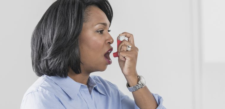 African American woman using asthma inhaler