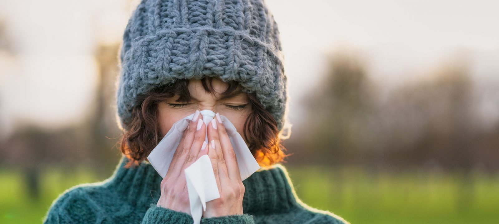 Close-up of a woman suffering from the symptoms of a cold outdoors during winter.