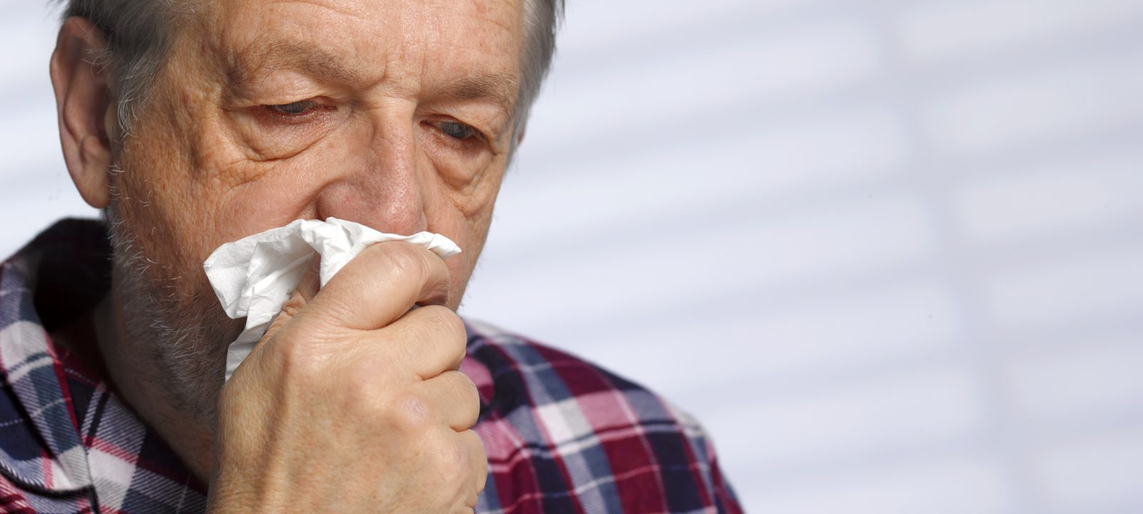 Senior man with a cold blowing his nose